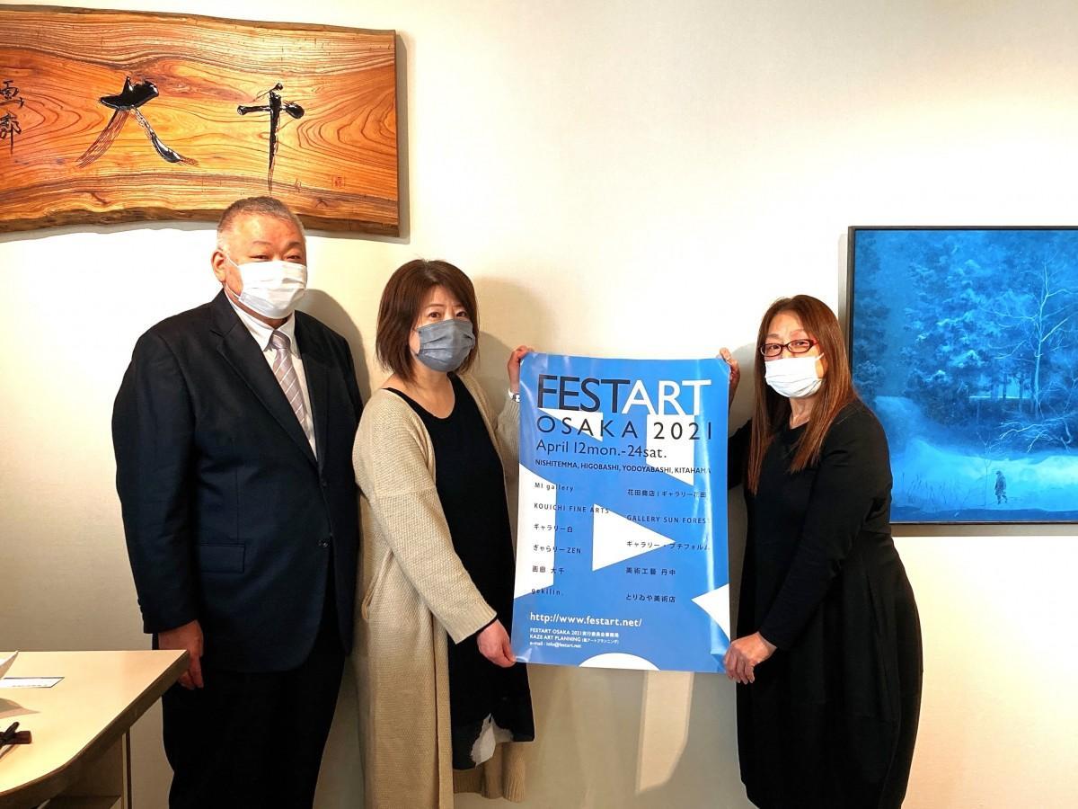 「フェスタアート2021年」のポスターを持つ「画廊 大千」の植松和美さん(右端)と尚子さん(中央)、植松和久さん(左端)。ポスターのロゴマークの青色は、医療従事者の支援を意味しているという