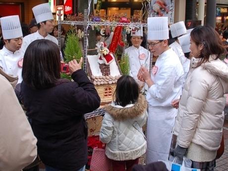 手渡されたクッキーの瓦を屋根に乗せる子ども=23日15時ごろ、仙台市青葉区の一番町4丁目商店街