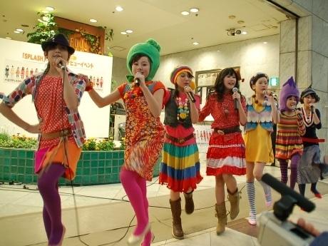 仙台市青葉区の藤崎百貨店前で「それゆけ!みちのく」を歌うSPLASH。メンバーが頭にかぶっているのは仙台名物「ずんだ」や「長茄子」のかぶり物