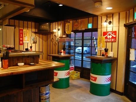 レトロな看板やドラム缶のテーブルが独特の味わいを醸す店内