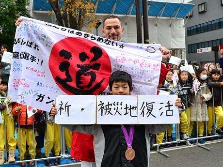 陸上競技男子ハンマー投げで銅メダルを獲得した室伏広治選手。被災地訪問で石巻の子どもたちから手渡された応援旗を広げた