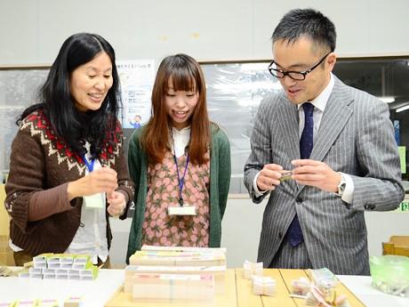 イラストレーターの泉友子さん(左)とたけのこスカーフさん(中央)に、完成したばかりの商品をお披露目する佐々木英明社長(写真右)