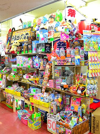 祭りの縁日をイメージしたディスプレー棚に所狭しと並べられた玩具。「並べ切れていない商品がまだまだたくさんある」という