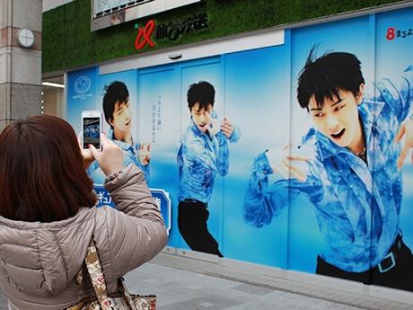 「仙台縁日」に掲出されている羽生結弦選手の巨大広告。ファンや市民が写真に収める姿が見られている