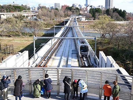 広瀬川橋りょうを走る車両を見下ろすことができる仙台国際センター駅。撮影スポットとして多くの人が集まっていた
