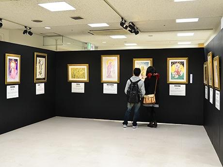 漫画家60人がそれぞれ独特のタッチで手掛けた仏画が並ぶ会場の様子