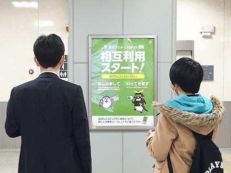 「イクスカ」「スイカ」相互利用開始を知らせるポスターを見る駅利用者