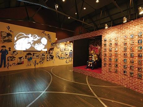 他会場の展示の様子。連載20周年スペシャルビジュアルのコナンと新一の等身大フィギュアが出迎える ©青山剛昌/小学館