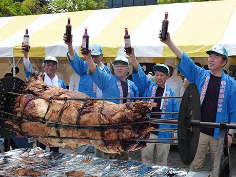 宮城県産黒毛和牛丸焼きに関係者が赤ワインをかけるセレモニー