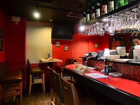 赤と黒を基調にした内装の「まぼ屋」店内。ホヤに合う日本酒の瓶が並ぶ