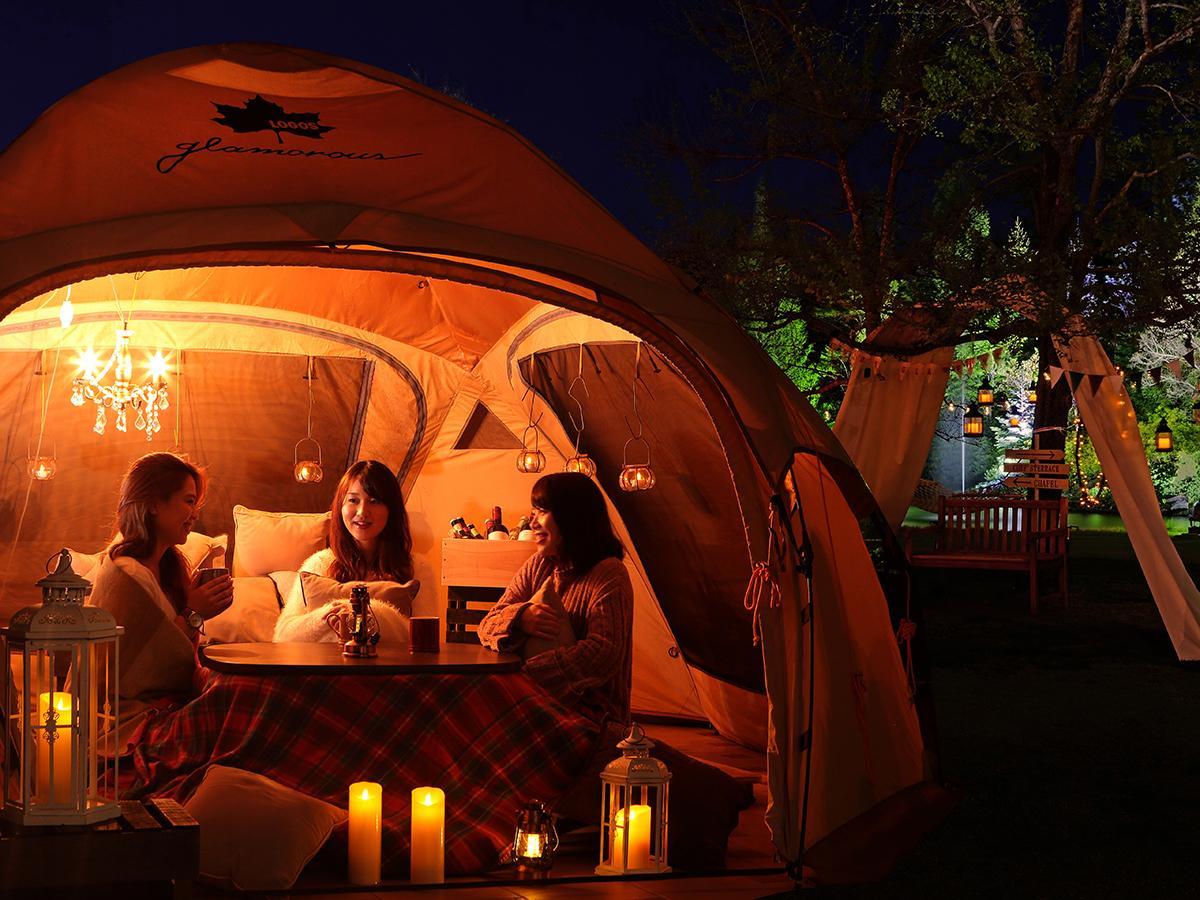 ガーデン内に設けられたこたつ付きのグランピングテント。ランタンの明かりが雰囲気を演出する