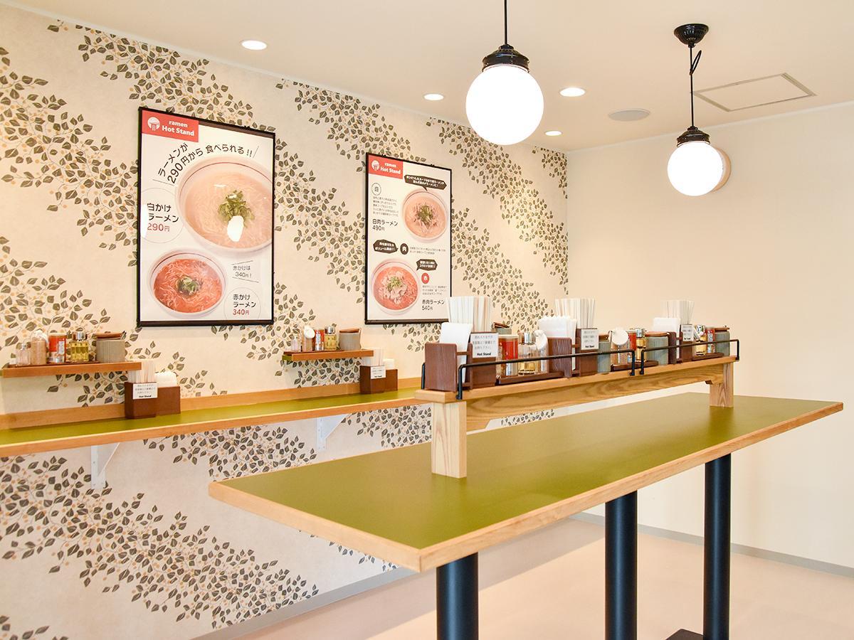 白を基調に、デザイン壁紙、明るい木目やグリーンのカウンターなど「ラーメン店らしくない」雰囲気に仕上げた店内
