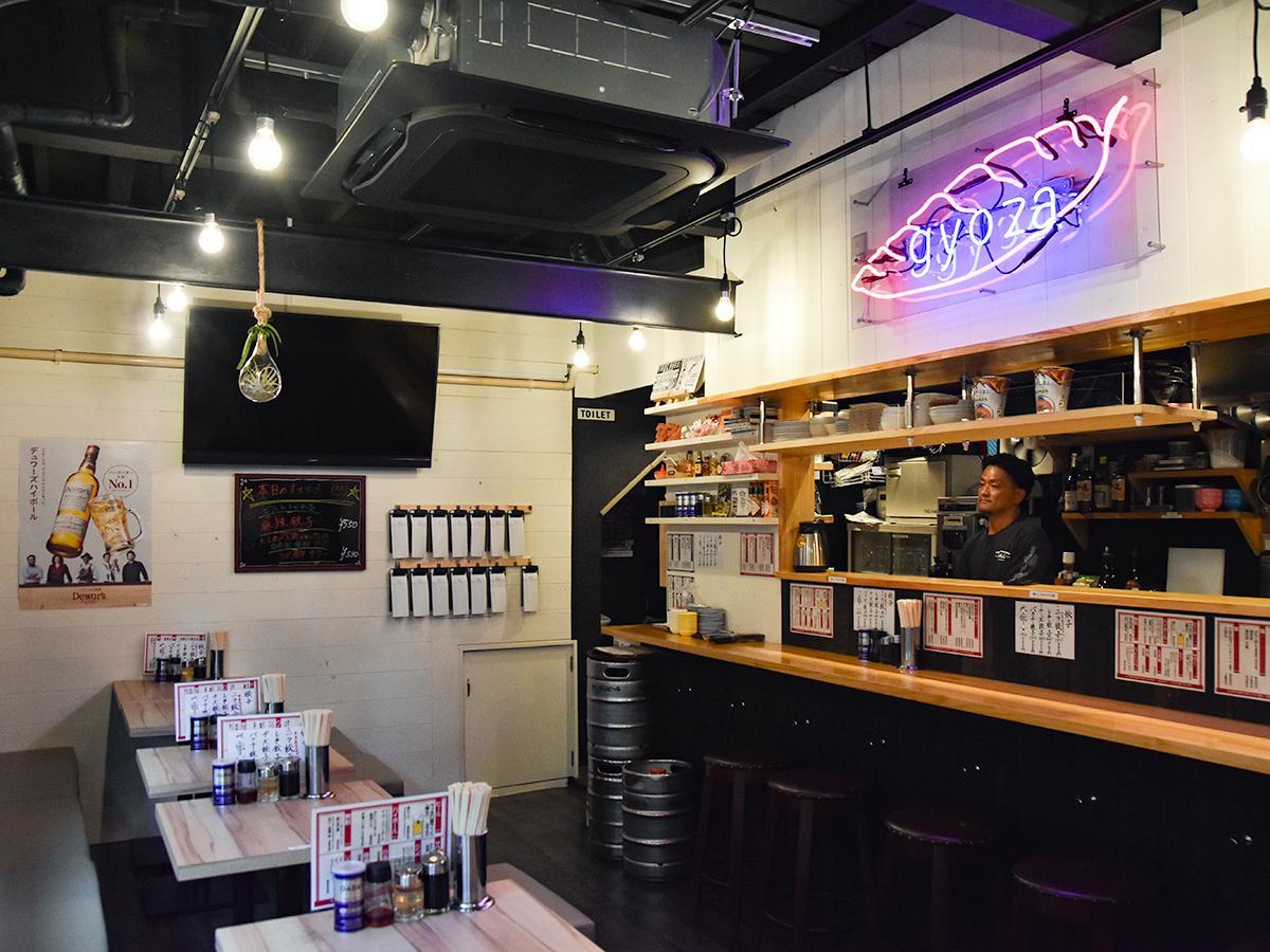 「gyoza」のネオン管が目を引く店内。厨房に立つ店主の吉沢さん