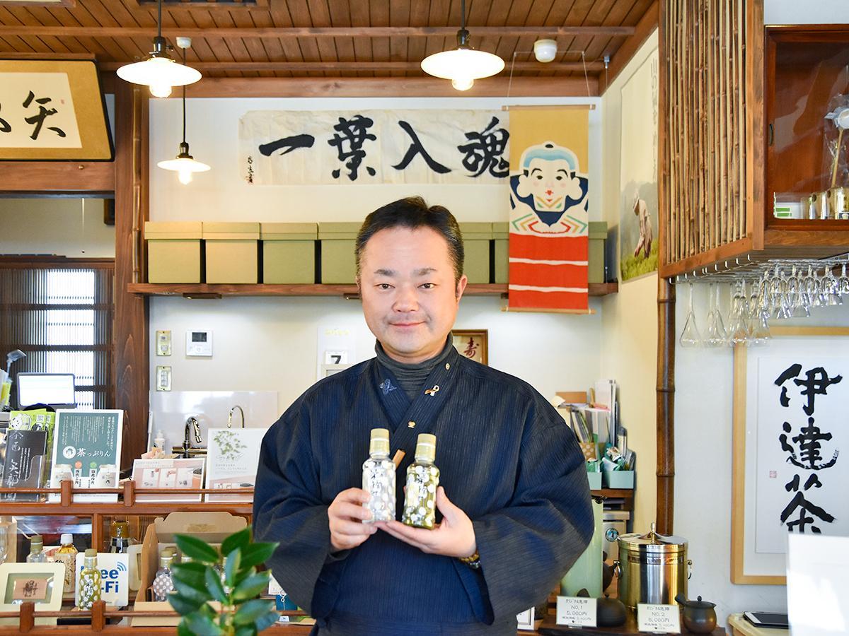 ペットボトル入り茶「茶摘み」を手に持つ「矢部園茶舗」3代目の矢部さん