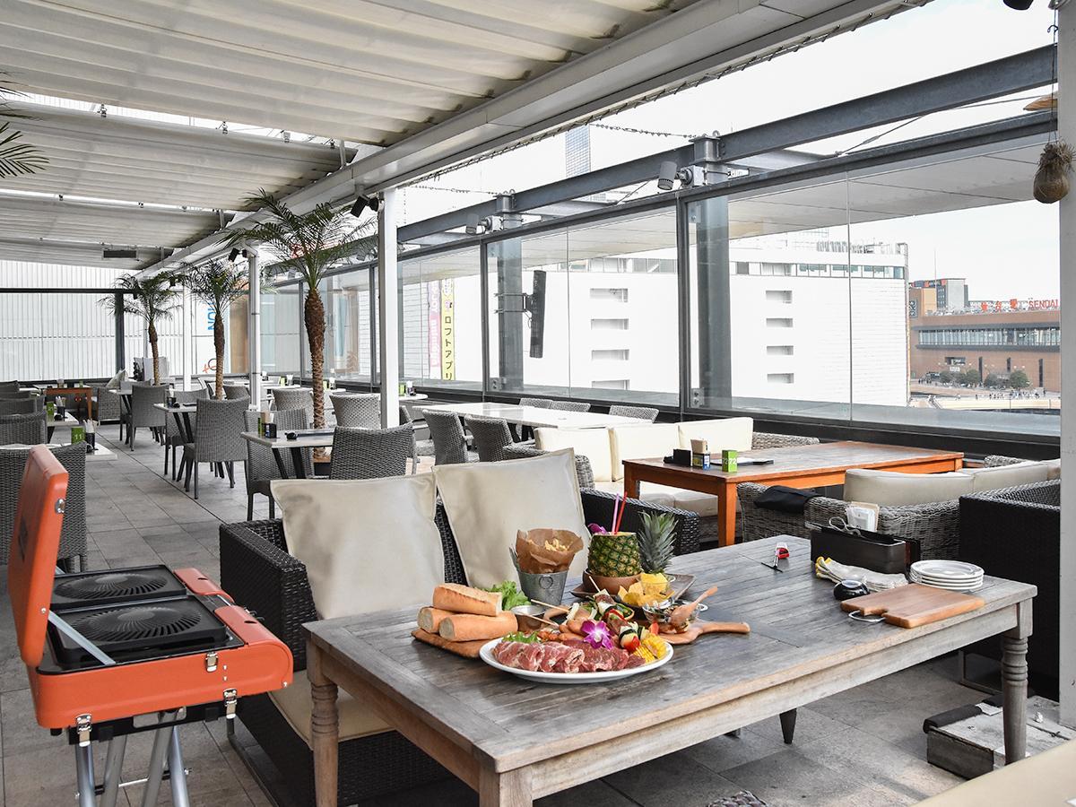 屋根付きのテラス席で駅前の風景を眺めながらバーベキューを楽しむアロハテーブルの「ハワイアンBBQ」