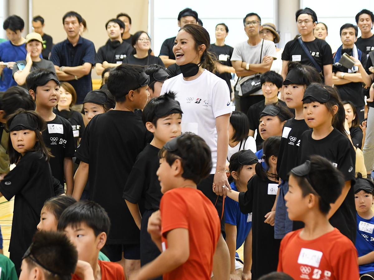 運動会で子どもたちと手をつないで競技を楽しむ宮里さん