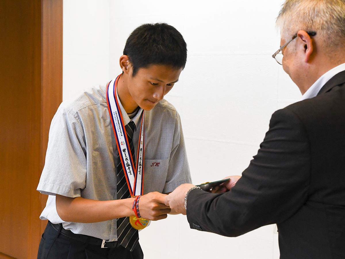松本教育次長から記念の盾を受け取る築館高の鵜澤選手