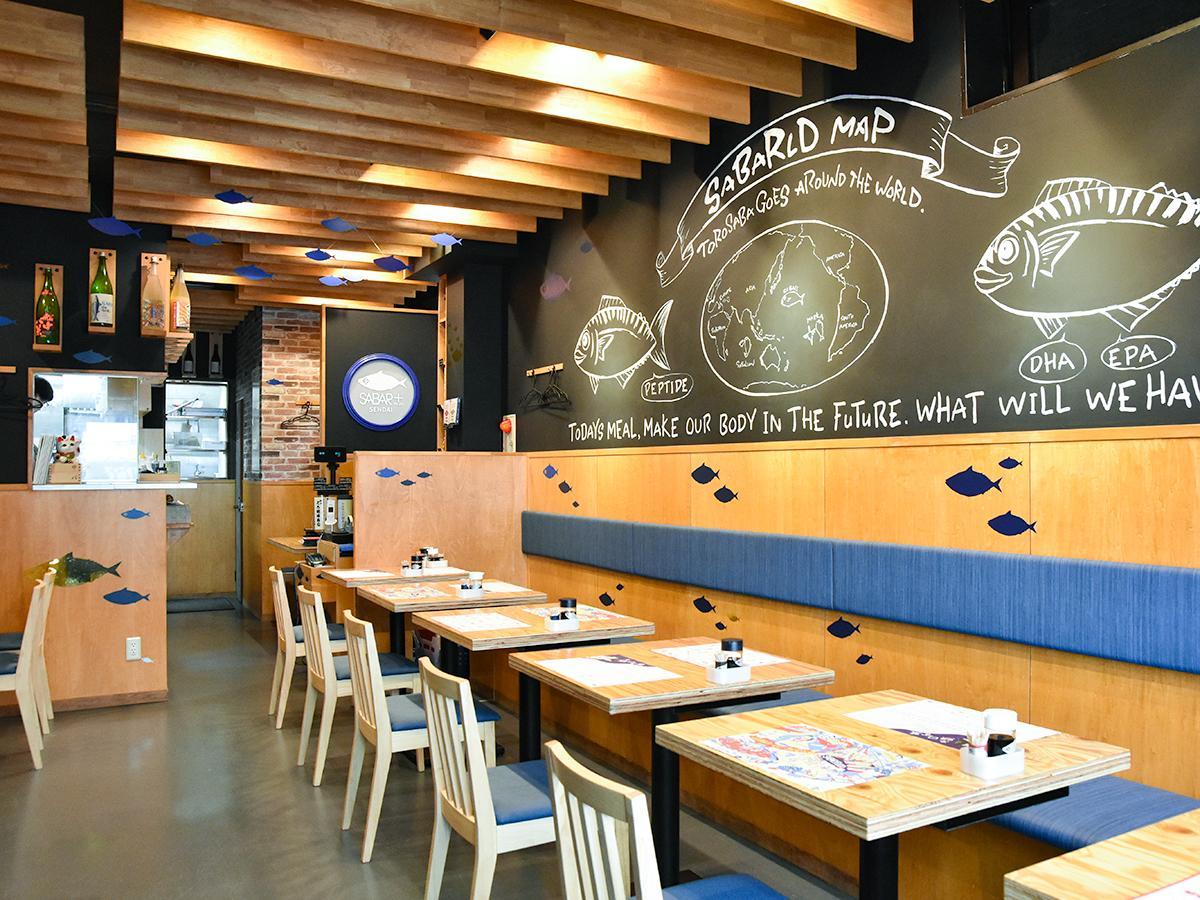 港町のバルをイメージした店内。壁の黒板には、金華サバが世界を旅して周った地図「サバールドマップ」が描かれている
