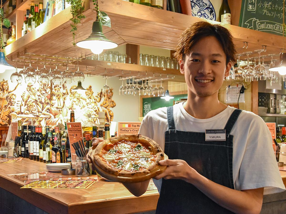 窯焼き500円ピザを薦める三浦店長。「多くのお客さまからの支えがあり、間もなく5周年を迎えることができる。これからもお客さまとの出会いを大切にして日々の営業に取り組んでいきたい」