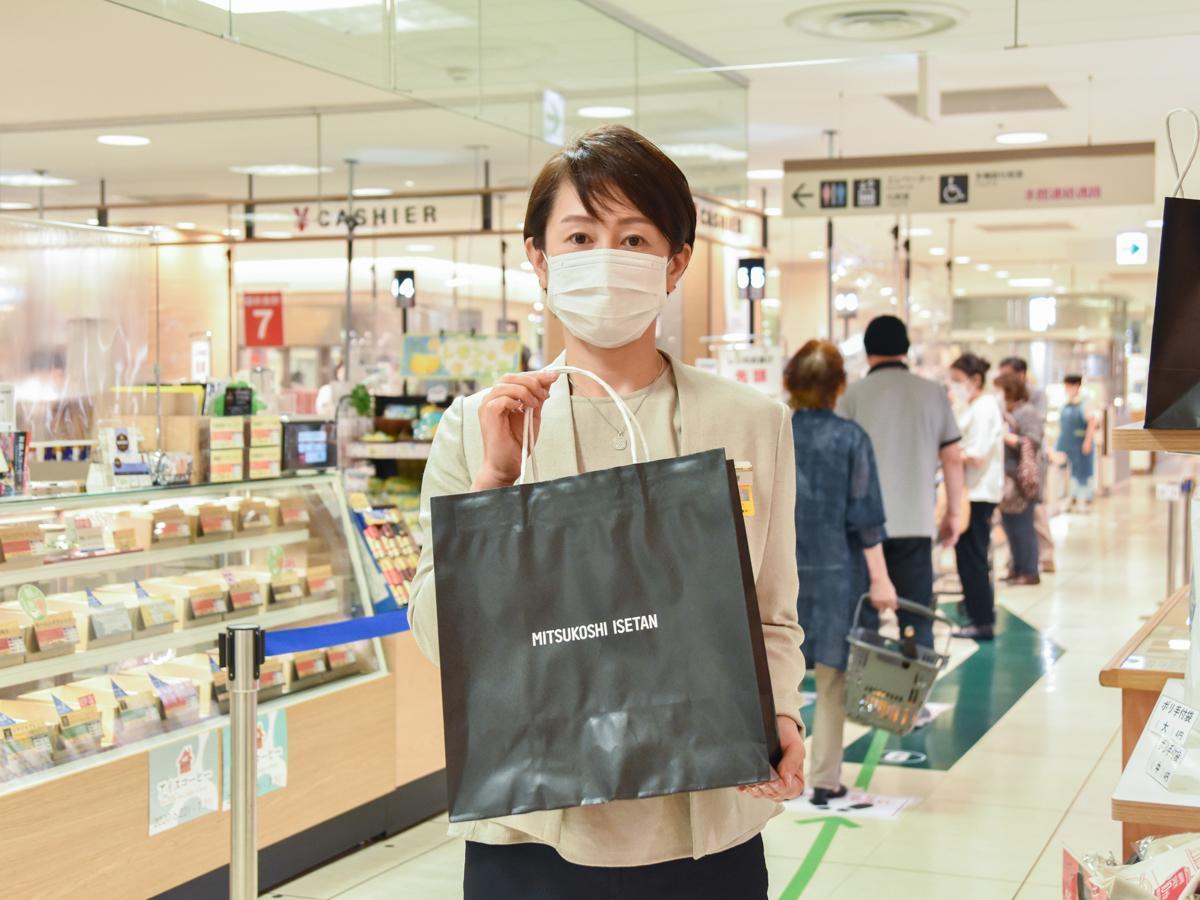 従来のものより強度と耐久性を上げた食品用紙製買い物袋を手に持つ仙台三越の相原さん