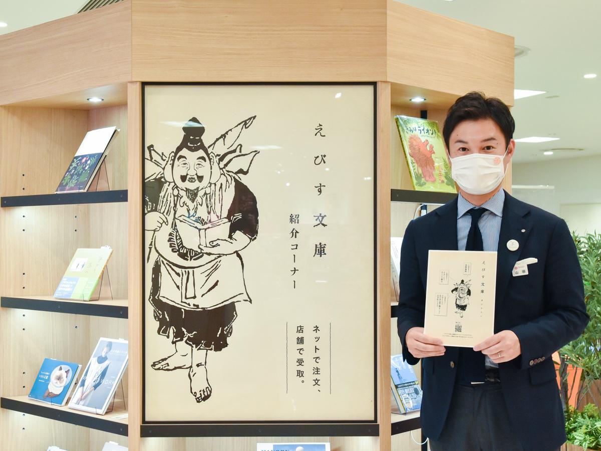 「えびす文庫オンライン」をPRする山田さん。アイコンには藤崎本館屋上に奉られている「えびす神社」の「えびす様」を採用。「運命の一冊と出合うすてきな導きがあるようにとの願いを込めた」