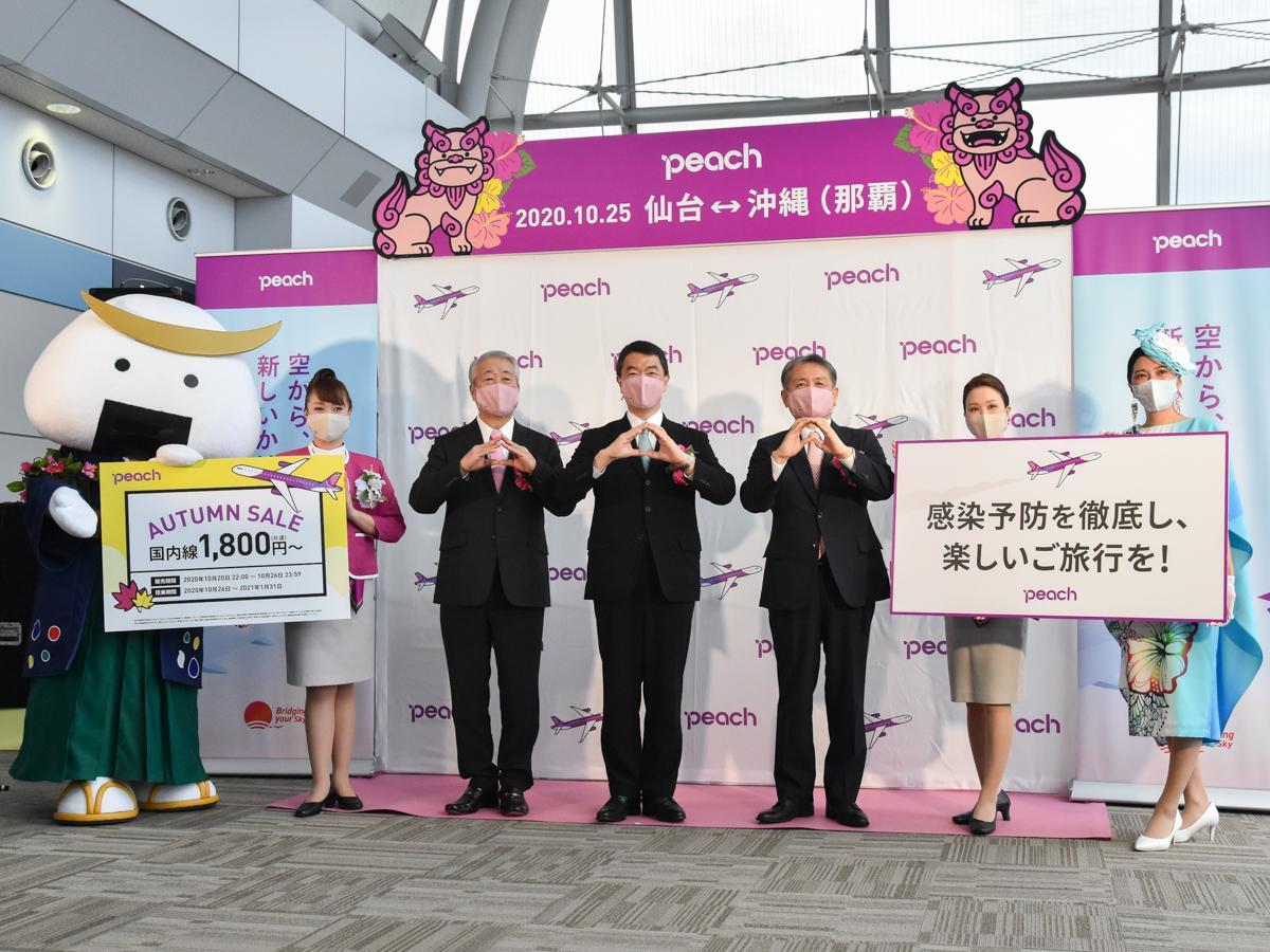ピーチの角城副社長(中央左)、村井知事(中央)、仙台国際空港の鳥羽社長(中央右)。両手で桃の形を作って就航を祝った
