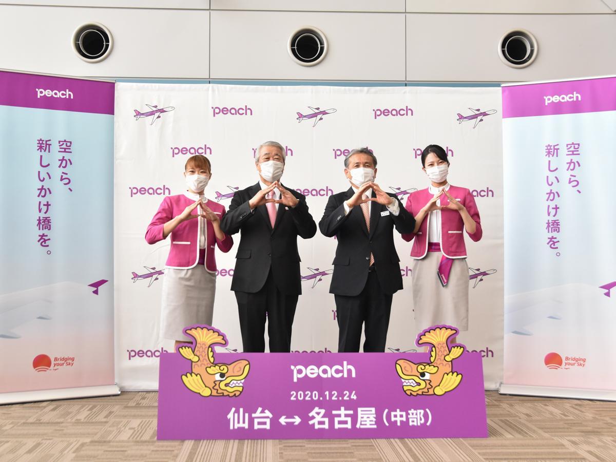 セレモニーに出席したピーチ・アビエーションの角城副社長(中央左)、仙台国際空港の鳥羽社長(中央右)。両端は愛知県出身の客室乗務員。両手で桃(ピーチ)の形を作って就航を祝った