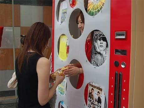 女性スタッフが中から商品を手渡す「有人自販機」