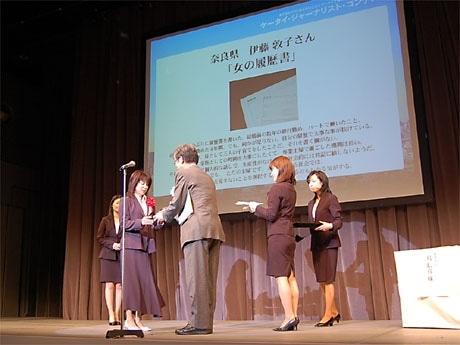 嶌審査委員長からトロフィーを受け取るグランプリ受賞の伊藤さん。スクリーンには伊藤さんの作品が