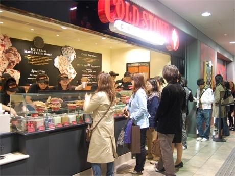 23日夕方、店の前は行列客でにぎわう。アイスを混ぜながらスタッフがオリジナルソングを歌う場面も