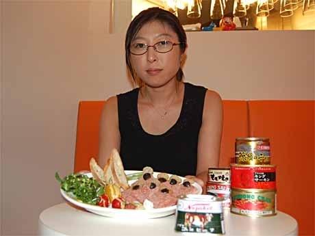 コンビーフ缶を丁寧に盛り付けた「缶詰メニュー」を手にするタカイさん。テーブルには「コレクション」の一部で2,000円以上する高級缶詰も