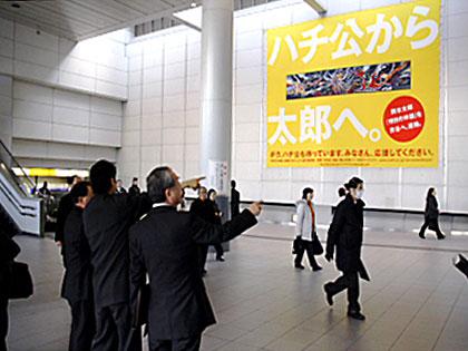 渋谷マークシティ連絡通路に視察に訪れた財団関係者の様子。黄色の懸垂幕がかけられた壁が、提案する招致場所