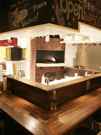 店内の様子。カウンター内には独自で開発したピザ焼き窯も