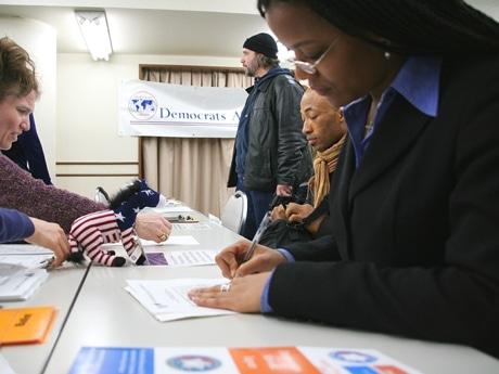 渋谷の「投票所」で書類に記入する在日米国人の様子