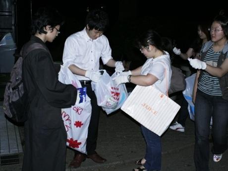 深夜の代々木公園でゴミ拾いを行う若者たち