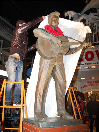 常連客らが見守る中、幕がかけられるエルビス・プレスリー像。18日に閉店した原宿「ロックンロール・ミュージアム」で