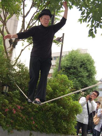 桜丘公園で綱渡りを披露した大道芸人フィリップ・プティさん。通行人や観客からは拍手も