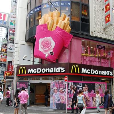 ピンク一色に衣替えした「マクドナルド渋谷センター街店」外観。ポテトの上に「Tシャツ」も