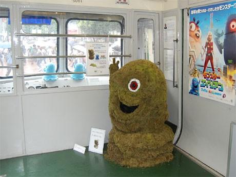 東急5000系車内に登場した「グリーン・ボブ」。車内には映画「モンスターVSエイリアン」のポスターも