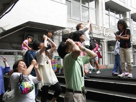 旧代々木高校跡地で行った「日食観望会」。雲の切れ間から見える「日食」を見上げる参加者たち