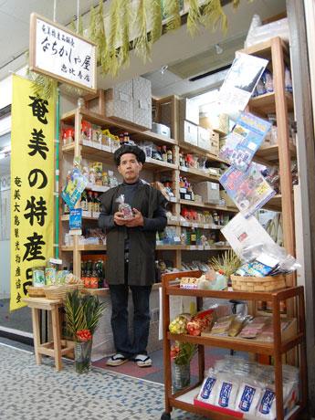 奄美の特産品販売店「なちかしゃ屋」がオープン。写真=大島紬をリメークした「えびす様風着物」を着た大井さん