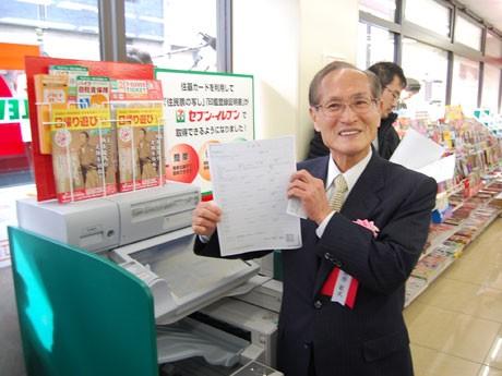 新型マルチコピー機を使って「住民票写し」交付のデモンストレーションを行う桑原敏武渋谷区長