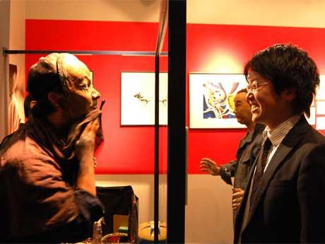 若木くるみさんの最新作「お面」のライブパフォーマンス。ハーフミラー越しに若木さん扮(ふん)する岡本太郎(左)、観客(右)が対峙(たいじ)し、刻々と顔が塗り替えられていく