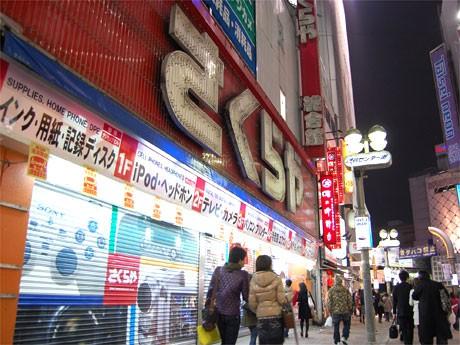閉店後、ネオンサインが消えた「さくらや渋谷店」。店頭に張り出された閉店案内のポスターをのぞき込む通行人の姿も