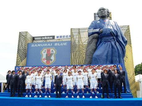 日本代表のユニホームをモチーフにした巨大龍馬像をバックにしたサッカー日本代表の23選手と岡田武史監督、エグザイルのメンバー