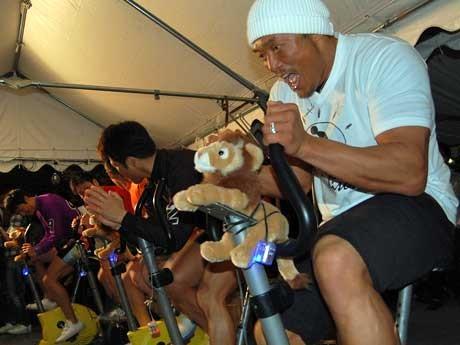 自転車をこいで人力発電する秋山成勲さんら