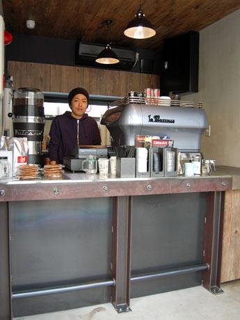 コンクリートの壁面や鉄骨、木材を基調にした店内。写真はバリスタ歴9年の加藤健宏さん