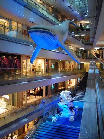 10メートルのザトウクジラのバルーンを吊るした吹き抜け大階段。20分毎に音と照明による環境演出「深海タイム」を実施