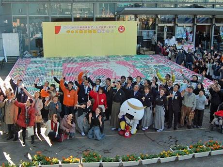 おむすび3万1100個を使って「おむすびアート」と参加者たち。宮城県観光キャンペーンキャラクターのむすび丸も