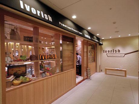 地階に位置する店舗外観。壁面にはフライパンなどを描いたロゴを掲出する